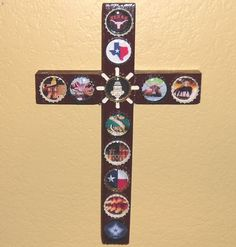 "This cross commemorates the Great State of Texas!  It is made of wood and painted a dark chocolate brown. Bottle caps are painted cream, black and gold. The center cap is accented with a replica of a spoke wheel from a spur.  Images include: longhorn head, map of Texas, cowboy boots, saddle, the Texas State Capital Building, longhorn, cowboys on horses, rattle snake, Texan flag and the logo of the Dallas Cowboys.  Measures approximately 11"" by 7"". $15.95"