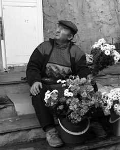 Flower seller, a man sitting on the ground and selling flowers at a market in Bucharest, Romania by Judi Saunders  http://fineartamerica.com/featured/flower-seller-judi-saunders.html