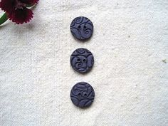 Stamped polymer clay buttons in dark purple with a bit of shimmer.