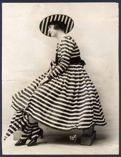 Woman in STRIPES:   stripes /straips/ (noun)  also striped /straipt/ (adjective) She is weared a STRIPED dress and STRIPED hat. Even her umbrella is STRIPED.