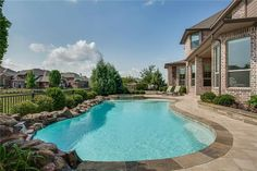 Beautiful free form pool with boulder coping, waterfall, raised spa and artistic pavers.