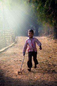 niño jugando con un palo con ruedas