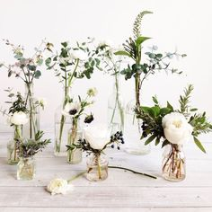 Cocktail Table Option--small bud vases with single blooms and wedding foliage would be the lowest price point in the range; I wouldn't do the tall ones, more so the shorter ones in the front. (Mixed Bottle Centerpieces)