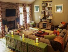 A Warm Living Room Featuring Green And Orange Earth Tones Patterned Curtains Rustic Wood Picture Collage Wall By Lindsay Hoekstra West Michigan