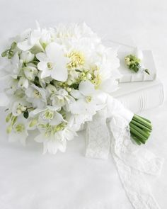 dahlias, white delphiniums, eucharis lilies, white orchids, and snowberry branches