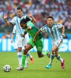 Okechukwu Uchebo of Nigeria controls the ball against Ezequiel Garay (L) and Ricardo Alvarez of Argentina during the 2014 FIFA World Cup Bra...