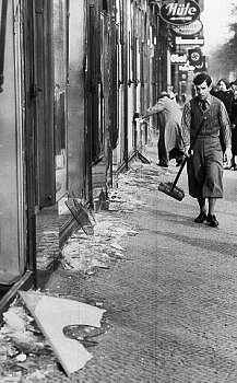 FILE - In this Nov. 10, 1938 file picture, a youth with a broom prepares to clear up the broken window glass from a Jewish shop in Berlin, the day after Kristallnacht