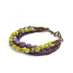 Pulsera de brillante y audaces en púrpura y verde lima. Había combinado de tres hilos de perlas de cristal y semillas y había añadido un montón de separadores de bronce para un look boho. La pulsera está acabada con un corchete de la langosta de bronce y tres enlaces de bronce gruesos para conectar a.  Si quieres añadir gran color a tu armario, este es el accesorio perfecto.  * 7 a 8 de largo (17.78 - 20.35 cm) ajustable  * cristal checo morado 8mm  * vidrio de chartreuse 4mm  Tu pulsera…