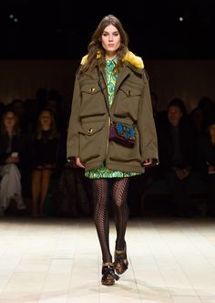 The Field Jacket in military green cotton canvas, worn over a turquoise and yellow jacquard shirt dress and teamed with platform loafers and The Patchwork bag. Discover the collection at Burberry.com