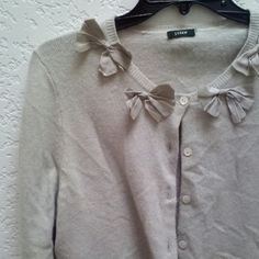 J. Crew Beige Cardigan with Silk Bows J. Crew cardigan in a lovely neutral beige/tan/oatmeal color. Bows line the neckline to give a sweet detail. There is no size tag and no fabric tag. But it does say dry clean only. My best guess is size small and wool. Please ask for measurements and any questions before purchasing. Thanks! J. Crew Sweaters