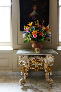 A bouquet of flowers on a rococo table at the Royal Showpieces exhibition at Paleis Het Loo /// Interiorator
