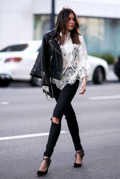 Jaqueta de couro jogada no ombro, blusa de renda com manga, calça preta rasgada no joelho, scarpin preta