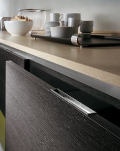 In the Flat Line composition with veneered, laminate and gloss  lacquered doors, the units are opened by means of under-top frames and handles set into the tops or sides of the fronts | When drawers and pull-out baskets are fitted, units are opened using  tip-on runners or push-pull knobs