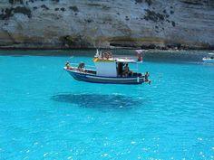 """イタリア:ランペドゥーザ島  地中海に浮かぶイタリアの小さなリゾート島。透明度が高すぎて、ボートが""""浮いているようにしか見えない""""と、有名。  Italy:Lampedusa island   The small resort island in Italy floating on the Mediterranean. It is too highly transparent and so it is famous for """"a boat is visible as it has only floated."""""""