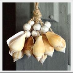 Natural canarium shells create this tassel cluster. Accent a door knob or window. Hang from a nautical hook or tie to a magazine basket. Add a beach vide to outdoor seating and hang from the back of a chair.