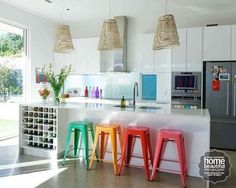 A row of stools adds a fabulous splash of colour at the kitchen bench.