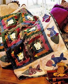 Here Fishy, Fishy  Quilt designer: Miriam Gourley   Quilt name: The Old Fishin' Hole, American Patchwork & Quilting 2004 Calendar  Anyone who loves the outdoors will smile at this scrappy quilt. Double-appliquéd fish swim around Log Cabin blocks tied with green yarn.