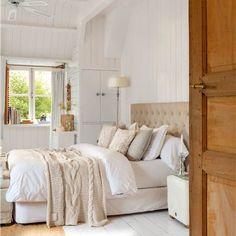 Dormitorio principal con ropa de cama en tonos blancos