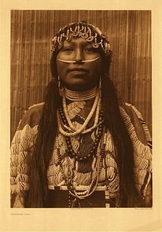 """Wishham girl,1910. """"The subject is clothed in a heavily beaded deerskin dress of the plains type. The throat is encircled by strands of shell beads of native manufacture, heirlooms which were obtained by the original Wishham possessor from the Pacific slope. Pendant on the breast are strands of larger beads of the same kind, as well as of various kinds brought into the country by the traders of the Hudson's Bay Company."""