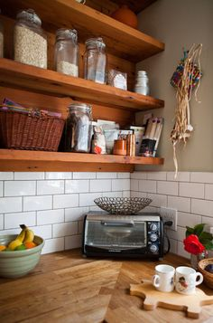 wood counters and white subway tile backsplash. Backsplash only as high as the first shelf. Veneer behind the shelves