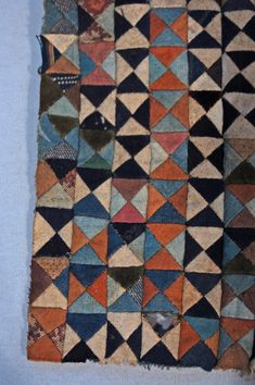 British Museum. Made by Nanai in Siberia. A cloth for domestic use (?), incomplete; an embroidery-sample. Made from small, triangular pieces of cloth, patched together to form squares (10 x 10).