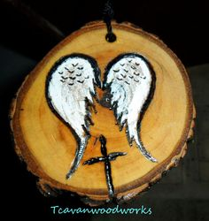 wings and cross rustic woodburned Christmas ornament #woodcross with angelwings burned on pecan wood tree slice #wingedcrossonwood http://etsy.comshop/tcavanwoodworks #uniquewoodgifts