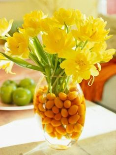 Place yellow flowers--in this case, double yellow tulips--in a clear vase with festive kumquats and water. They'll add a touch of spring to your dining table or any corner of your house.