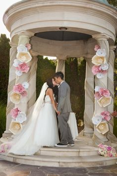 giant paper flowers frame the ceremony (photo by elle jae weddings)