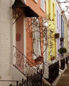 heartofapril:  enchantedengland:   Kensington Church Street,in London England. The district of Kensington inwest London is an affluent area withhigh-end retailers and attractions including the Natural History Museum,Hyde Park, Kensington Palace, the Victoria and Albert Museum,and these gorgeous pastel rowhouses with those fabulous Art Nouveau railings and wrought iron gates.  image by Ceclia Condal