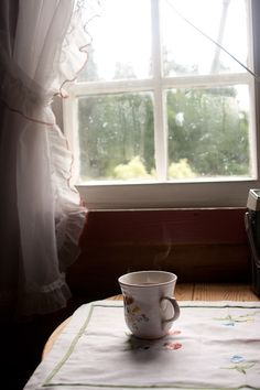 Sipping tea while gazing out the window.