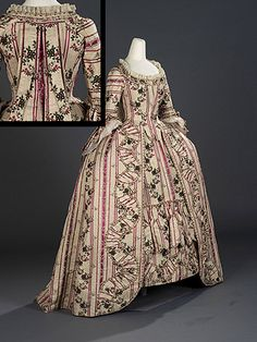 This cream coloured corded silk twill dress is typical of 1775 to 1785 France. The longitudinal stripes overlaid with delicate floral meander brocade pattern appears to be embroidered onto the dress, but is actually woven into the fabric. The engageants on this dress are paper replicas, although the matching petticoat is original.