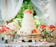 A gorgeous four tiered wedding cake dons textured white icing and fresh peach flowers.