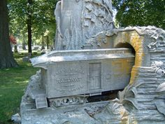 """Gravestone of George S. Bangs located in Rosehill Cemetery, Chicago. @ the base of the large carved stone tree stump is scale model of railway mail car entering a tunnel. The railway car & tunnel entrance appear to be out of proportion w/ tree & carved foliage & plants. Bangs is credited w/ """"Fast Mail"""" trains, they were specially designed trains consisting of only mail cars w/ expedited schedules designed to accommodate the needs of the Post Office rather than the needs of the traveling…"""
