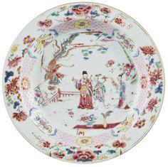 Assiette peinte dans les émaux de la famille rose à décor de personnages en porcelaine de Chine de la Compagnie des Indes d'époque Yongzheng Assiette décorée dans les émaux de la famille rose, le bassin peint d'un phœnix en vol, accompagné d'un soleil et de nuages, survolant trois personnages richement vêtus et une barrière sur une terrasse arborée,