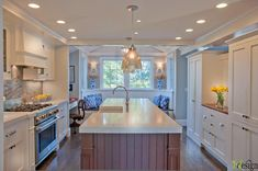 Fabulous open plan kitchen with white ceiling height cabinetry paired with brushed nickel hardware from Restoration Hardware and Misty Carrera Caesarstone countertops.
