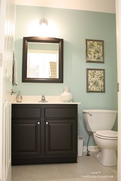 Love this post from The Powder Room is FINISHED! I love the wall color (Valspar Glass Tile), the cabinet color (Behr Premium Plus in Black Jet) and the art she did using framed fabric treated with matte Mod Podge. Bad Inspiration, Bathroom Inspiration, Bathroom Ideas, Bathroom Vanities, Bathroom Makeovers, Budget Bathroom, Bathroom Drawers, Dark Vanity Bathroom, Powder Room Vanity