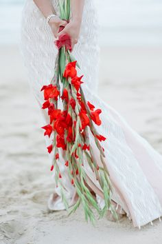 Pantone fiesta floral arrangement for a beach inspired ceremony. The contrast of these against the wedding gown are striking. Credit: www.wantthatwedding.co.uk #WedPin #AcademyLive #Wedding