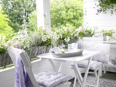 A double balcony terrace has painted walls and woodwork white and aligned with an outdoor turf plastic carpet and the shelves on the wall, a side table, a simple whitewashed bistroset and comfortable pillows. Hanging baskets filled with herbs and flowering plants on the balcony edge complete the setting