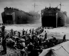 """Two Coast Guard-manned LST's open their great jaws in the surf that washes on Leyte Island beach, as soldiers strip down and build sandbag piers out to the ramps to speed up unloading operations."" 1944."