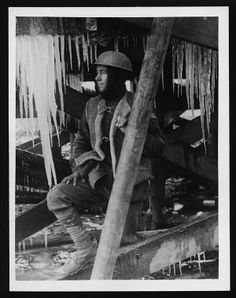 Young soldier surrounded by icicles, France. The soldier is wearing a cloth wrapped round his head under his helmet. He has a thick sheepskin waistcoat over his ordinary uniform which is fastened with leather straps. His hands and face still look quite grubby and he is smoking a cigarette. He is sitting amongst what appears to be the complex supports of a wooden structure. The icicles hanging from this are thick and long. This photograph, clearly illustrates the harsh realities at the Front.