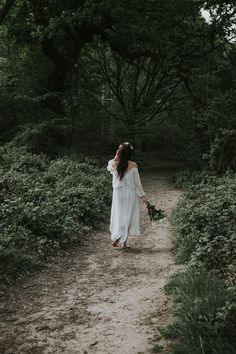 Beautiful artistic wedding photography ideas for bridal portrait sessions. Our bride looked like the perfect boho girl, walking around the woods bare foot wearing a simple wedding dress and holding a white rose bouquet.