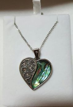 Inlaid Paua shell ornate halved heart pendant with inset glass stones, on 18 trace chain. Pendant 37mm.  Paua shell is sourced from New Zealand is a Maori tradition. Paua shell is deemed as a good luck positive shell and makes the perfect gift for occasions such as weddings, birthdays and Christmas. Each piece of paua shell is never the same. Our Paua shell is sustainably sourced & is nickel, cadmium & lead compliant. Also Hypoallergenic  All items sent in presentation box.  To see more of…