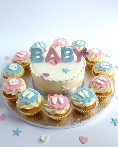 Baby Shower Round-about, 15cm cake with 12 cupcakes by Karen's Cakes. Handmade fondant blue and pink baby topper