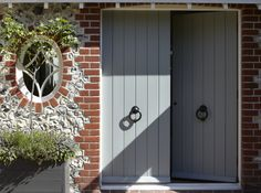 double front door, painted wood, plain boards, grey/gray, dual black iron door knockers, red brick, flint wall, square planter box, plant