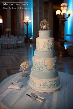 "This Cinderella wedding cake was inscribed with ""Happily Ever After"" on three of the tiers. The other tieres were decorated with an ornate carriage swirl. This fondant creation was made up of two double tiers and four regular tiers for a unique look."