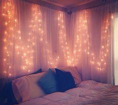 Christmas lights behind hanging sheer fabric.