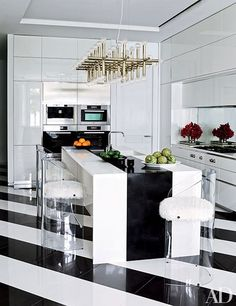 A modern black and white kitchen featuring white lacquer cabinetry and striped floors | archdigest.com