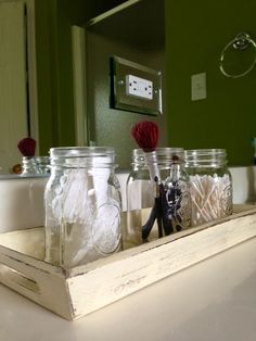 Distressed wooden tray with mason jars for the bathroom.