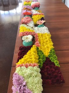 Long tablescape. Expeanded, teak midcentury modern table holds long, shallow copper trays which, in turn, hold blankets of pave'd flowers of a variety of mums, spray roses, crespida, dianthus, and gerbera.
