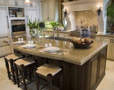 Custom kitchen island with an oak stained cabinet and beige granite counter that contrasts against the white of the main kitchen cabinetry.